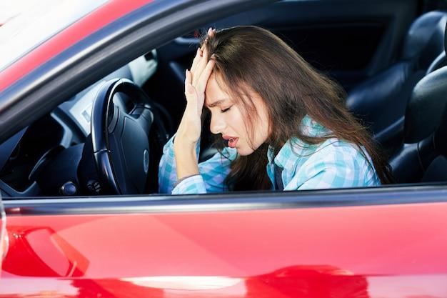 Profil der nervösen frau, die rotes auto fährt, stress während des fahrens. angespannte frau, die mit geschlossenen augen, staus auf der hand lehnt. kopf und schultern der brünetten frau im auto