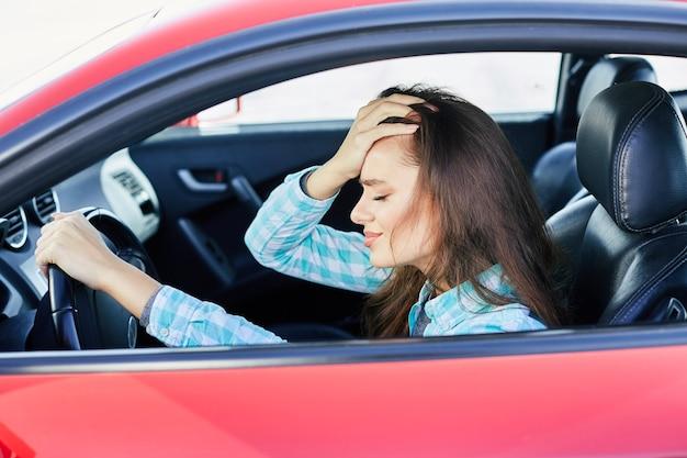 Profil der verärgerten frau, die rotes auto fährt, stress während der fahrt. angespannte frau, die mit geschlossenen augen, staus auf der hand lehnt. kopf und schultern der brünetten frau im auto