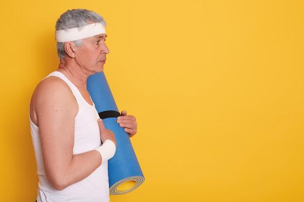 Profil des älteren mannes, der weißes t-shirt und stirnband trägt, yogamatte in händen hält und geradeaus schaut