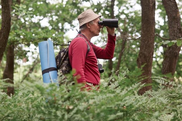Profil des alten reisenden, der alleine kampiert, umgebung prüft, durch fernglas schaut, den aktiven lebensstil liebt