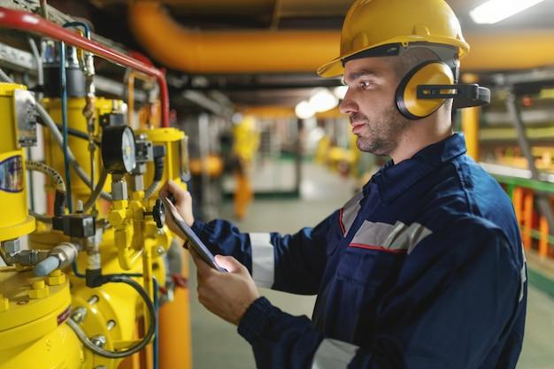 Profil des fleißigen arbeiters mit helm, antifones und im schutzanzug, der luftdruck auf kesseln prüft, während er in der schwerindustrieanlage steht