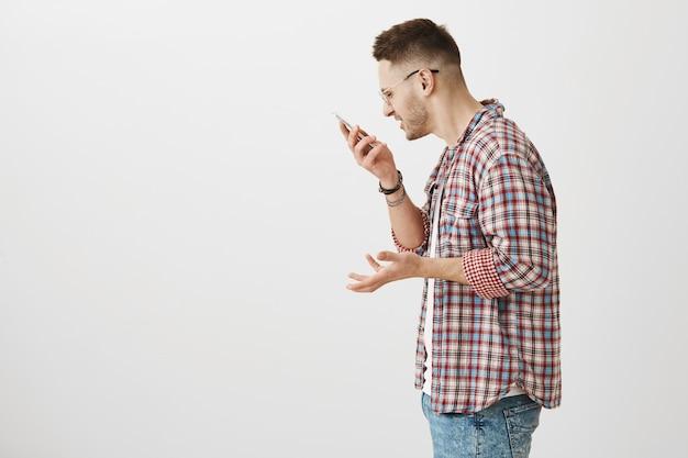 Profil des gestörten wütenden jungen kerls, der mit seinem telefon aufwirft