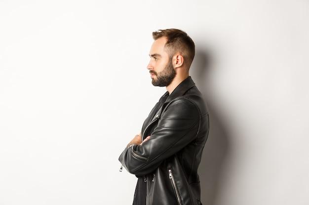 Profil des hübschen ernsten mannes in der lederjacke, links schauend, händchenhalten auf der brust zuversichtlich, weißer hintergrund.
