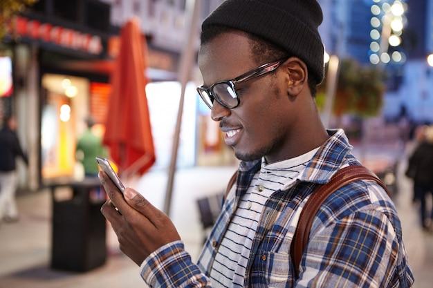 Profil des jungen afroamerikanischen touristen in der stilvollen brille und im hut unter verwendung des smartphones, der versucht, herberge oder hotel zu finden, um nacht zu verbringen, während in einer anderen fremden stadt während seines roadtrips angehalten