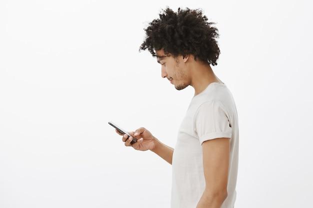 Profil des jungen städtischen mannes, der handy, sms-freund auf social media verwendet, bankkonto prüfend