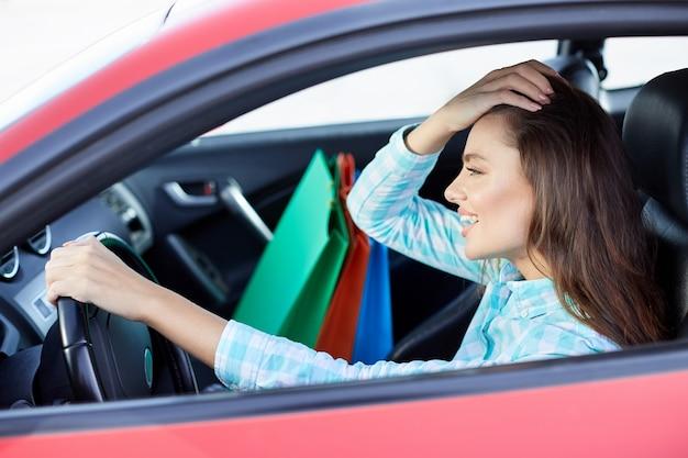 Profil des mädchens, das im roten auto sitzt, glücklicher fahrer. frau, die nach vorne schaut und lächelt. kopf und schultern der glücklichen frau, die das ruder hält und vom einkaufen zurückkommt