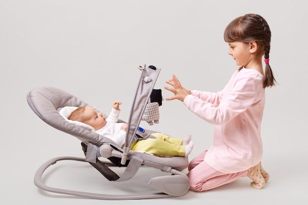 Profil des niedlichen kleinen mädchens mit zöpfen, das rosa freizeitkleidung trägt, die mit neugeborenem babyschwestermädchen spielt, das im türsteherstuhlspiel liegt