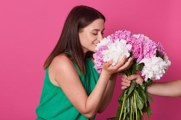Profil des niedlichen lächelnden mädchens mit geschlossenen augen, die blumen mit bunten blütenblättern riechen, sie mit beiden händen berühren, in hochstimmung sein, unbekannte hand, die bouquet lokalisiert über rosa hält
