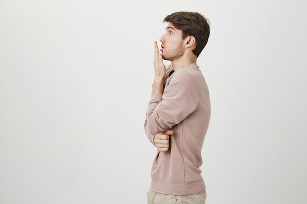 Profil des schockierten kerls, der nach luft schnappt, mund mit der hand bedeckt und nach links starrt