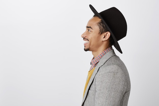Profil des schönen afroamerikanischen mannes im stilvollen hut, der glücklich lächelt und links schaut