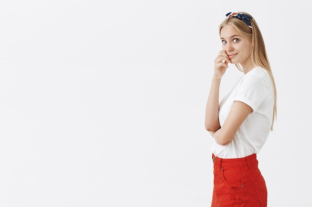 Profil des schönen jungen blonden mädchens, das gegen die weiße wand aufwirft