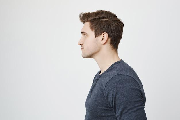 Profil des schönen stilvollen jungen mannes, der links schaut