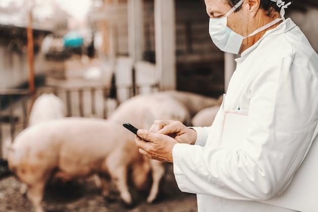 Profil des tierarztes im weißen kittel und in der maske auf gesicht, das klemmbrett unter achsel hält und smartphone verwendet