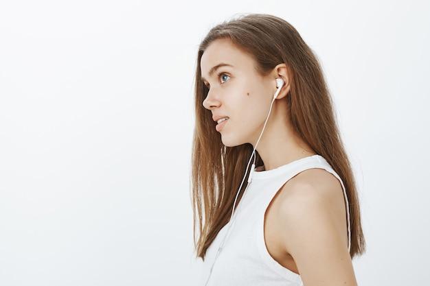Profil des verträumten attraktiven mädchens, das podcast oder musik in den kopfhörern hört