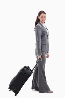 Profil einer geschäftsfrau, die mit einem koffer lächelt