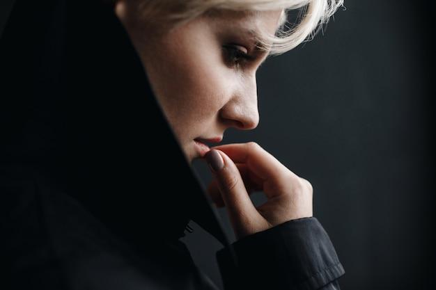 Profil einer schönen durchdachten frau, die ihre lippen berührt