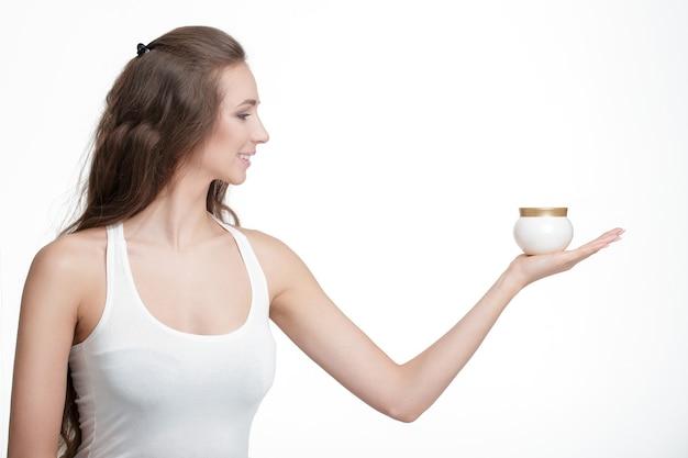 Profil einer schönen frau mit einem glas kosmetischer creme