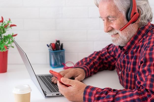 Profil eines älteren mannes, der social-media-inhalte mit dem mobiltelefon auf dem schreibtisch mit laptop-computer durchsucht