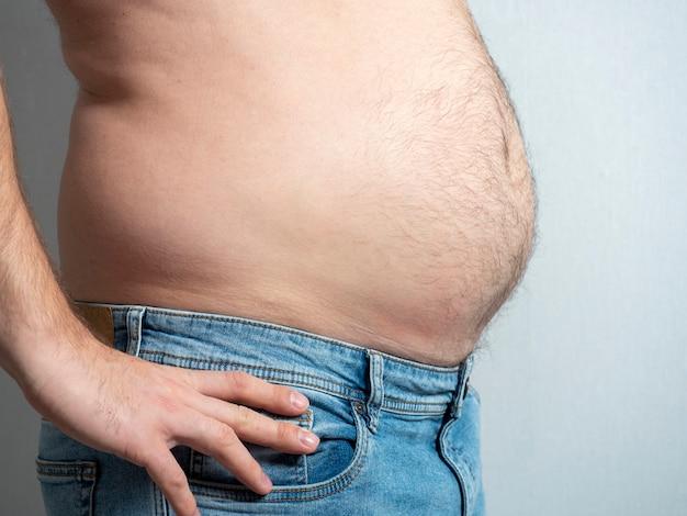 Profil eines dicken mannes in jeans. das problem der fettleibigkeit bei männern.