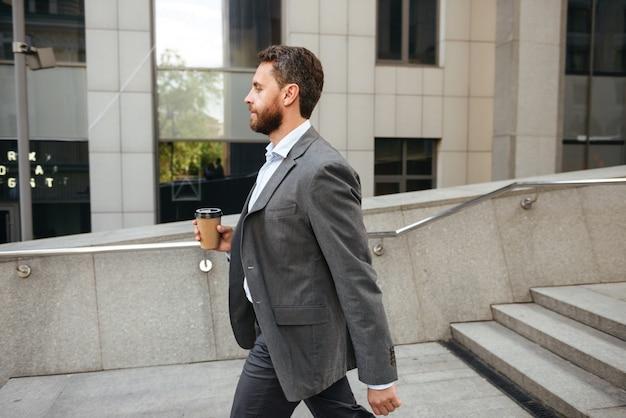 Profil erfolgreicher unternehmer oder direktor mann im grauen anzug, der kaffee zum mitnehmen hält und entlang straße mit modernem geschäftszentrum geht