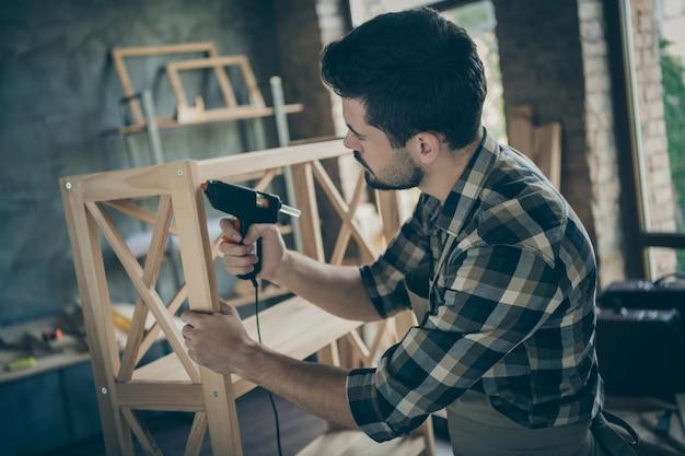 Profil hübscher kerl, der bücherregal handgemachtes design zusammenbaut, das unter verwendung der bohrerverbindungsteile holzindustrie nach hause holzwerkstatt drinnen zusammenbaut