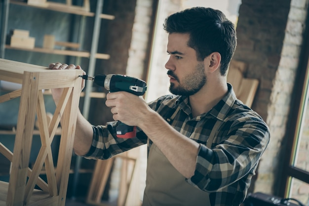 Profil hübscher kerl, der bücherregal handgemachtes design zusammenstellt, das unter verwendung der holzarbeitswerkstatt der bohrholzindustrie drinnen zusammenbaut