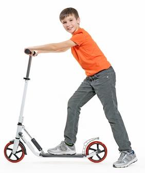 Profil in voller länge eines glücklichen kindes, das einen roller lokalisiert auf weißem hintergrund reitet