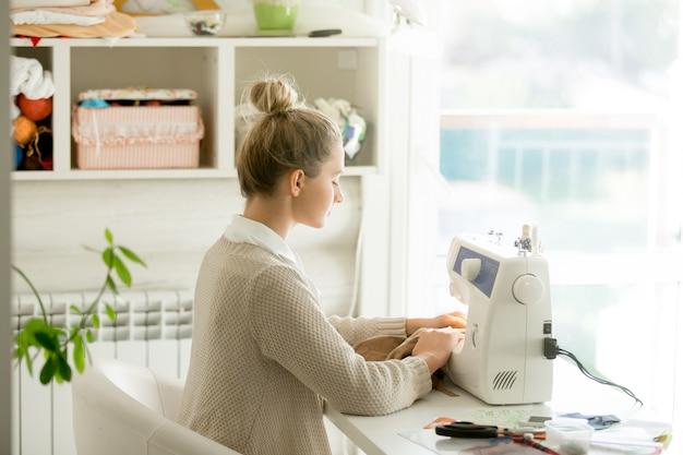 Profil porträt einer jungen attraktiven frau auf nähmaschine