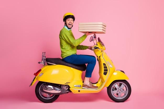 Profil seitenansicht porträt des fröhlichen kerls, der moped fährt, das kuchen bringt