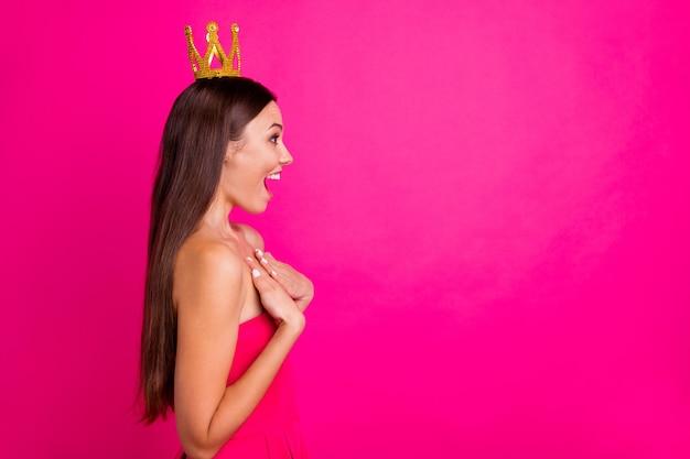 Profil seitenansicht porträt von ihr sie schöne attraktive schöne fröhliche fröhliche fröhliche langhaarige mädchen tragen krone ausdruck freude isoliert auf hellen lebendigen glanz lebendigen rosa fuchsia farbe hintergrund isoliert