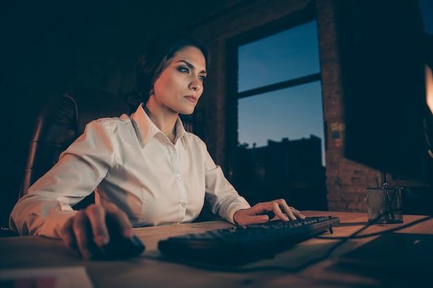Profil seitenansicht von ihr sie schön attraktiv konzentriert konzentriert geschäftsfrau agent makler top-manager fleißig in unternehmensagentur bei nacht dunklen arbeitsplatz station drinnen