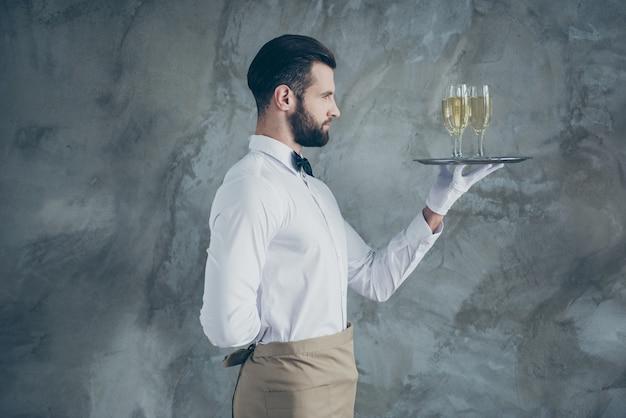 Profil-seitenfoto des attraktiven gutaussehenden in der schürzenhalteplatte mit gläsern des champagners mit der isolierten grauen farbe der betonwandwand der borste