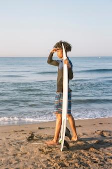 Profil von afro-surfer mit surfbrettern mit blick auf den horizont am strand bei sonnenaufgang.