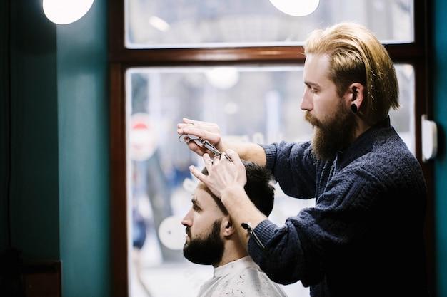 Profil von friseur schneide mannes haar