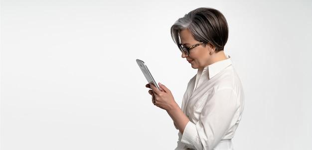 Profilansicht der ernsthaften frau, die mit digitalem tablett arbeitet