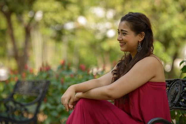 Profilansicht der glücklichen jungen schönen indischen frau, die am park sitzt