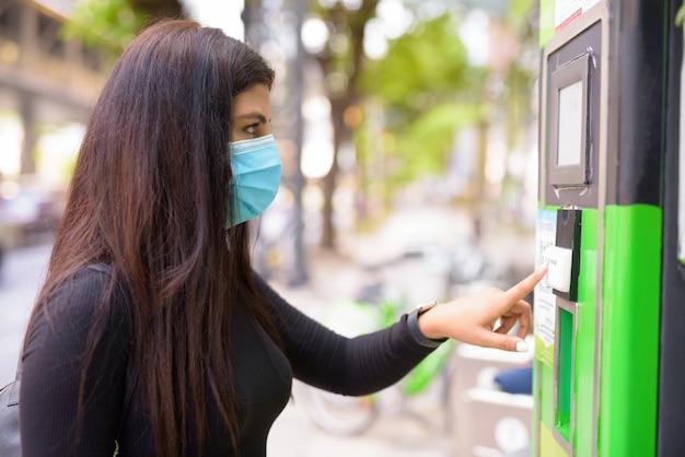 Profilansicht der jungen inderin mit maske, die fahrrad an der öffentlichen fahrradservice-station mietet