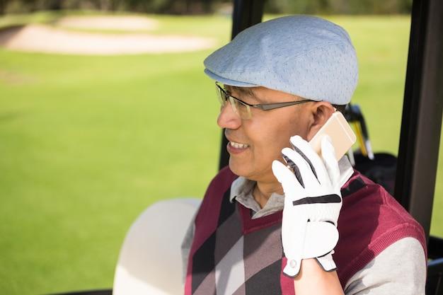 Profilansicht des golfers, der lächelt und anruft