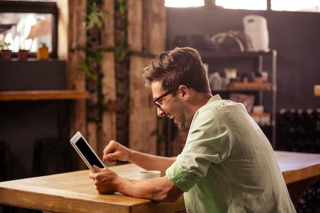 Profilansicht des hipster-mannes unter verwendung der tablette