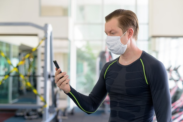 Profilansicht des jungen mannes mit maske unter verwendung des telefons im fitnessstudio während des coronavirus covid-19