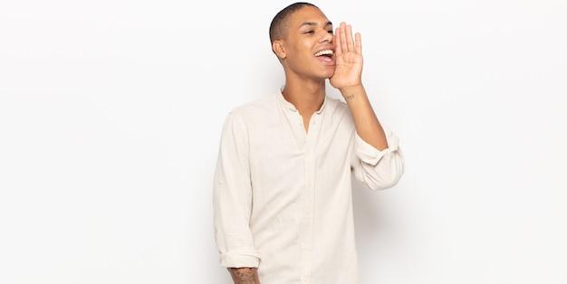 Profilansicht des jungen schwarzen mannes, der glücklich und aufgeregt aussieht, schreit und ruft, um raum auf der seite zu kopieren