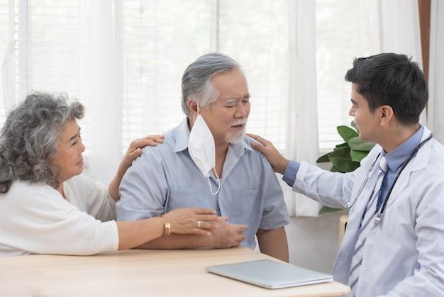 Profilansicht des kaukasischen kardiologen, der den arzt mit seinem älteren älteren asiatischen patienten mit hilfe der dokumentdatei während der untersuchung und der einnahme von medikamenten zu hause konsultiert. selektiver fokus auf älteren patienten