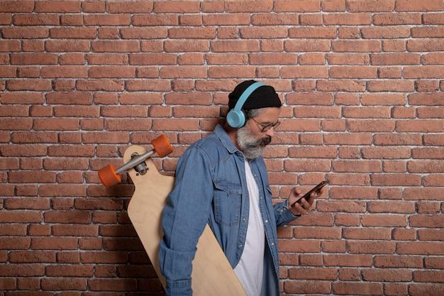 Profilansicht des modernen mannes mit bart, hut, kopfhörern und longboard, die telefon auf backsteinmauer betrachten