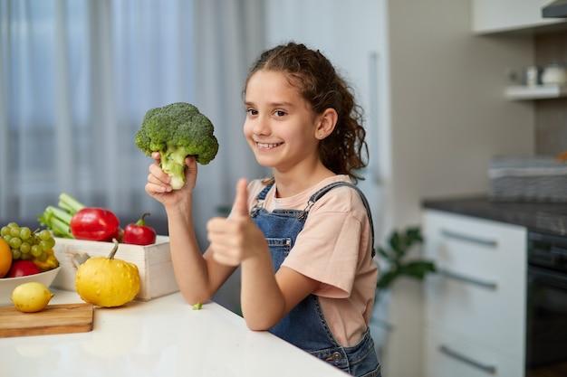 Profilansicht eines kleinen mädchens mit lockigem haar, das eine jeans und ein t-shirt trägt, einen brokkoli hält, einen daumen zeigt und am tisch in der küche sitzt.