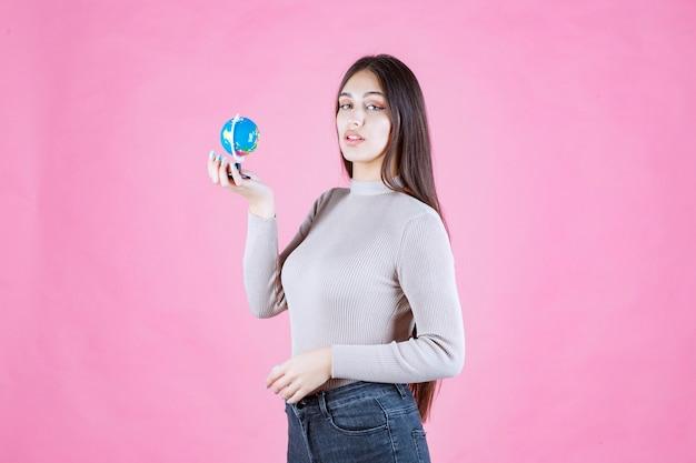 Profilansicht eines mädchens, das einen mini-globus mit vertrauen hält