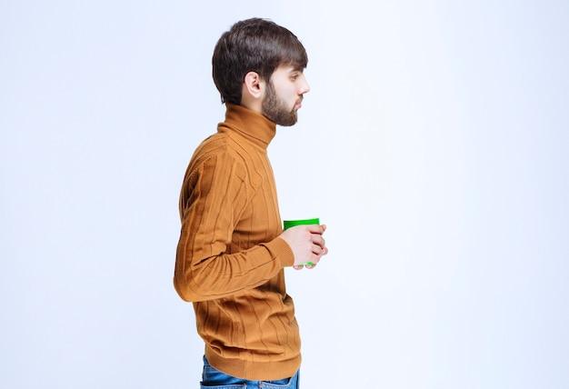 Profilansicht eines mannes, der kaffee hält und trinkt.