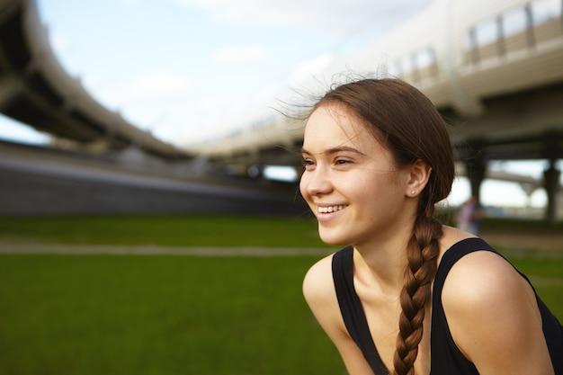 Profilaufnahme des attraktiven jungen kaukasischen weiblichen athleten mit dem dunklen haar, das im geflecht gesammelt wird, breit lächelnd, schönes sommerwetter während der übung im freien im stadion genießend. sport und fitness