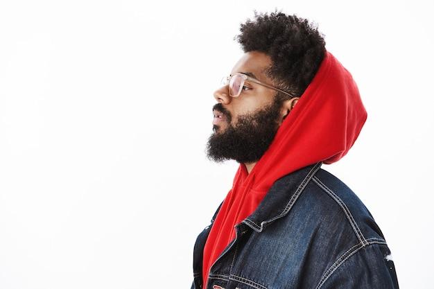 Profilaufnahme eines coolen und stylischen, selbstbewussten und selbstzufriedenen afroamerikanischen rap-sängers, der einen hoodie und eine jeansjacke trägt und mit erhobenem kinn nach links selbstbewusst über grauer wand aussieht
