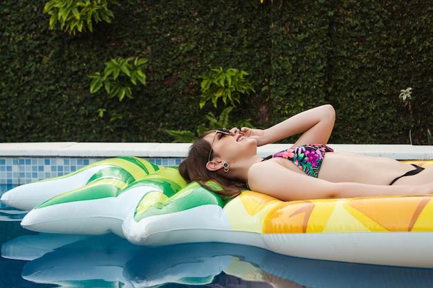 Profilaufnahme eines schönen glücklichen mädchens mit sonnenbrille, die auf ihrem schwimmer im pool liegt.