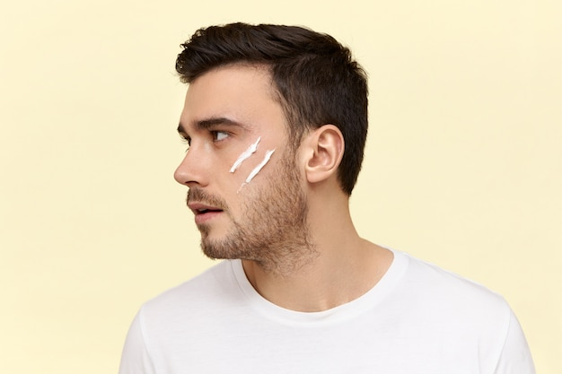 Profilaufnahme eines selbstbewussten, gut aussehenden jungen europäischen mannes mit stilvoller frisur und borste, die am morgen vor der arbeit feuchtigkeitscreme vor dem spiegel aufträgt.
